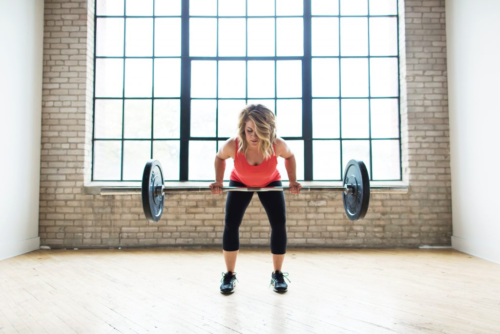 fitness woman holding barbell performing workout